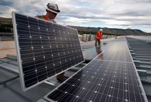 Two men carrying commercial solar panels